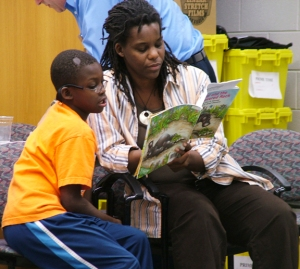 "Aminata Cairo, anthropologist and scholar for Prime Time Family Reading Time, models for families how to sit with their children and share a book as the storyteller reads aloud, ""Anansi and the Moss Covered Rock."" Kathleen Pool"